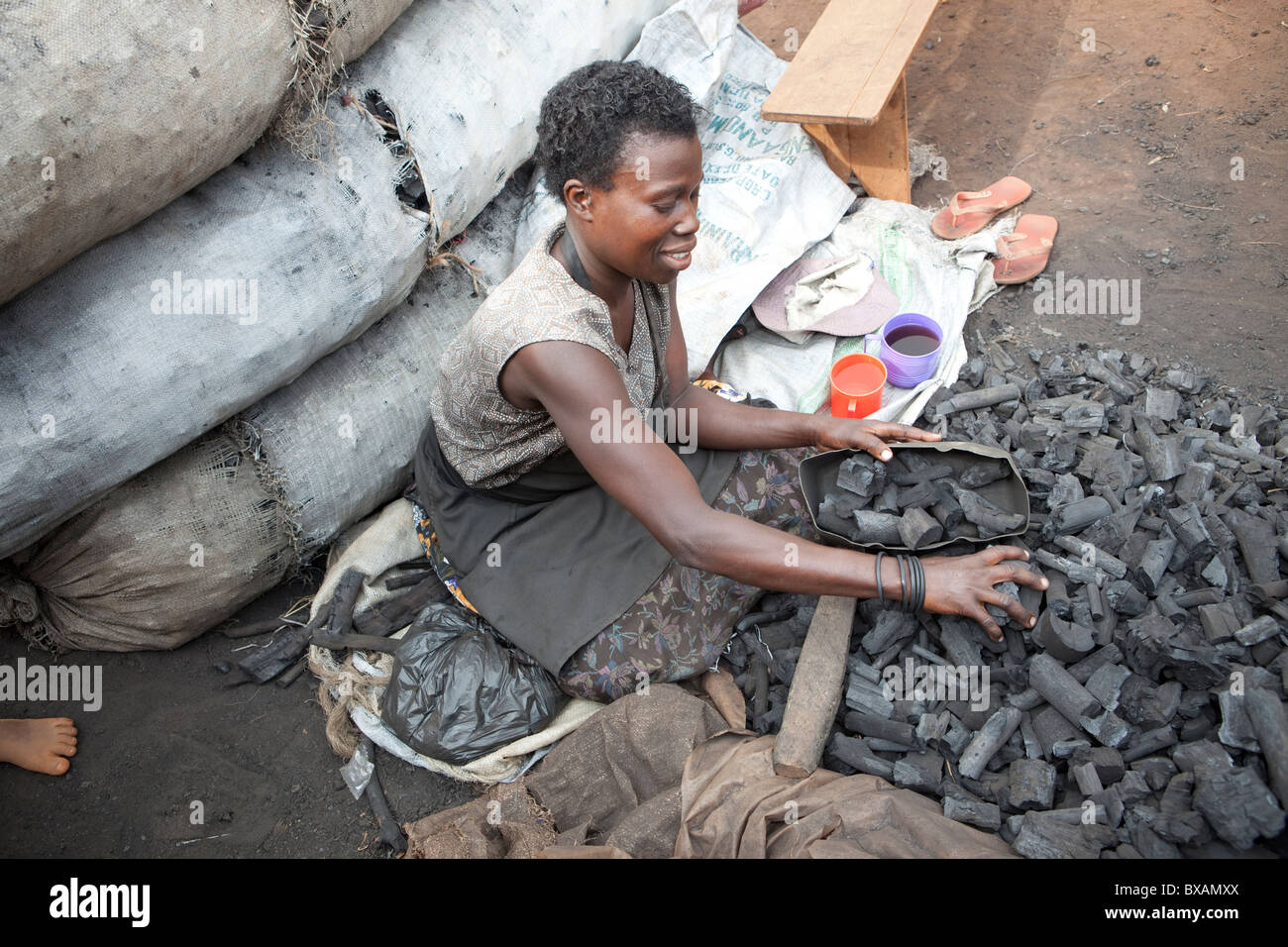 A woman sells charcoal on the streets in Jinja, Uganda, East Africa. - Stock Image