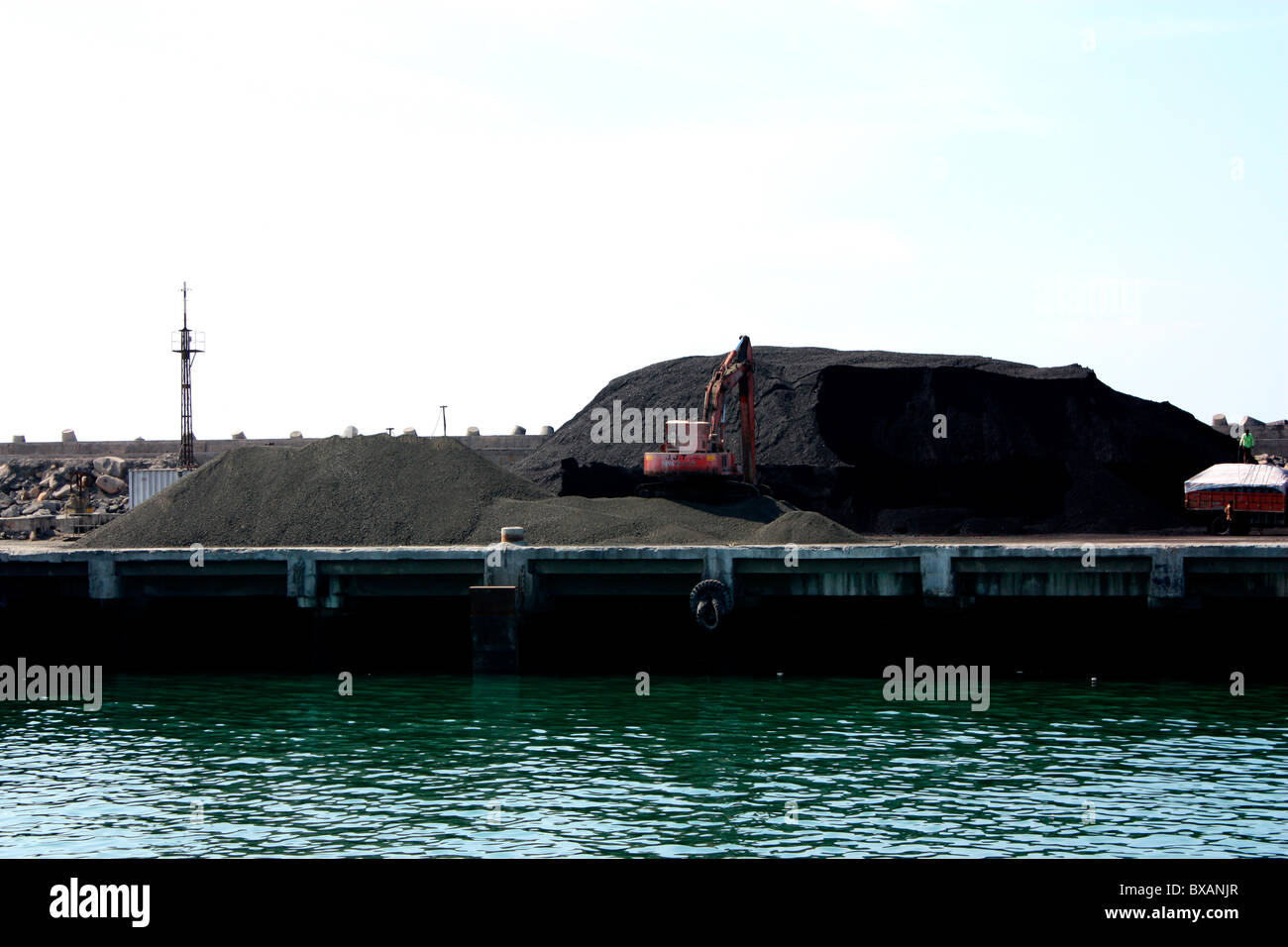 Dumping of iron ores at Porbandar port - Stock Image