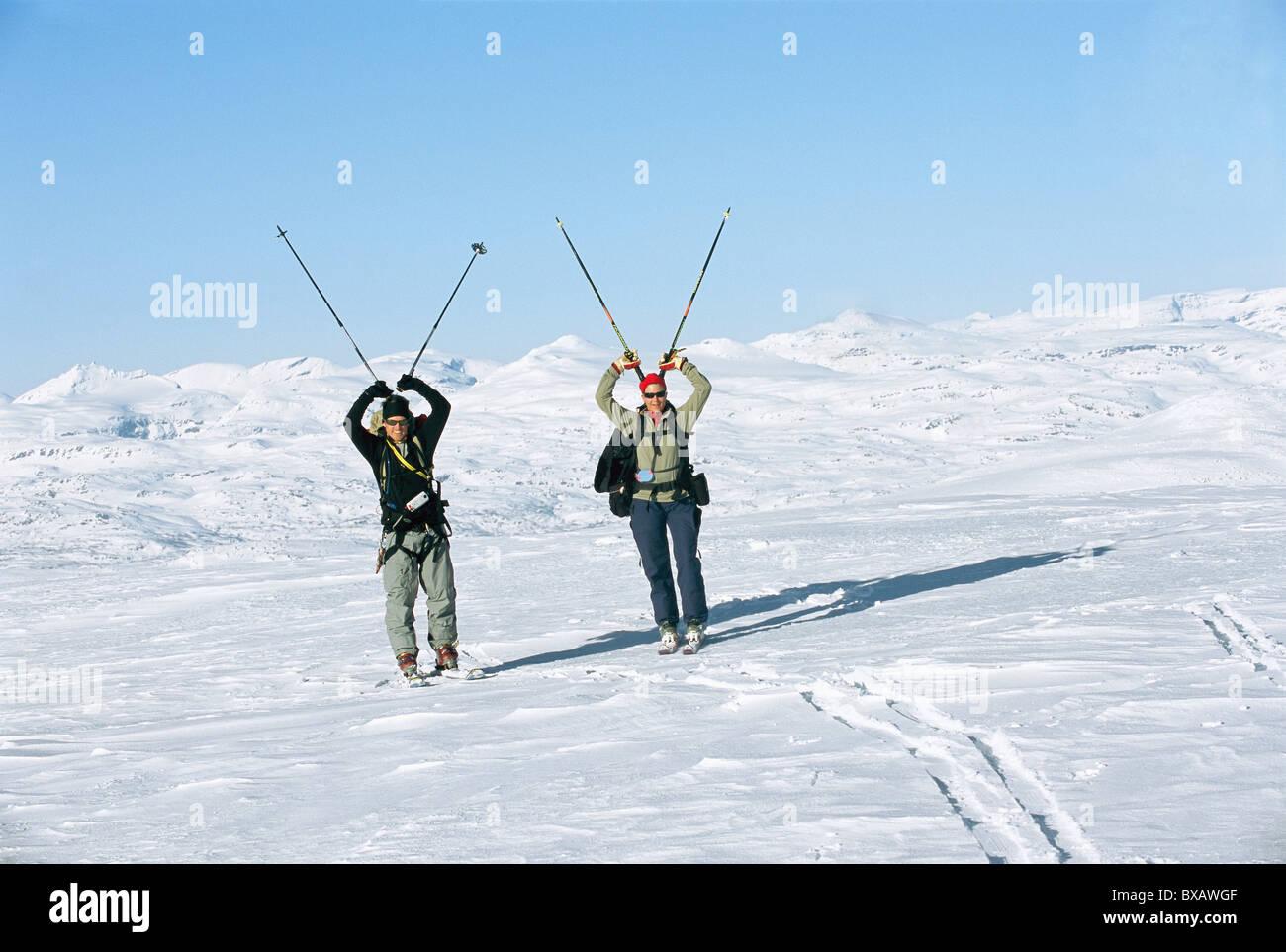 Tourists carrying ski poles - Stock Image