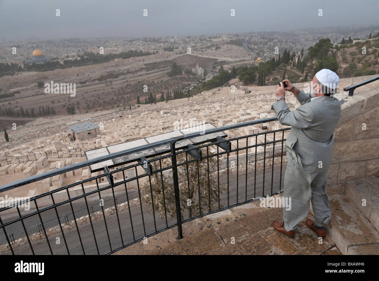 muslim tourist taking a picture of the Old City from the viewpoint at Mount of Olives. Jerusalem. israel - Stock Image