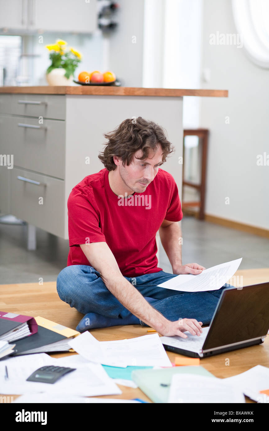 Mid-adult man working from home, using laptop on kitchen floor - Stock Image