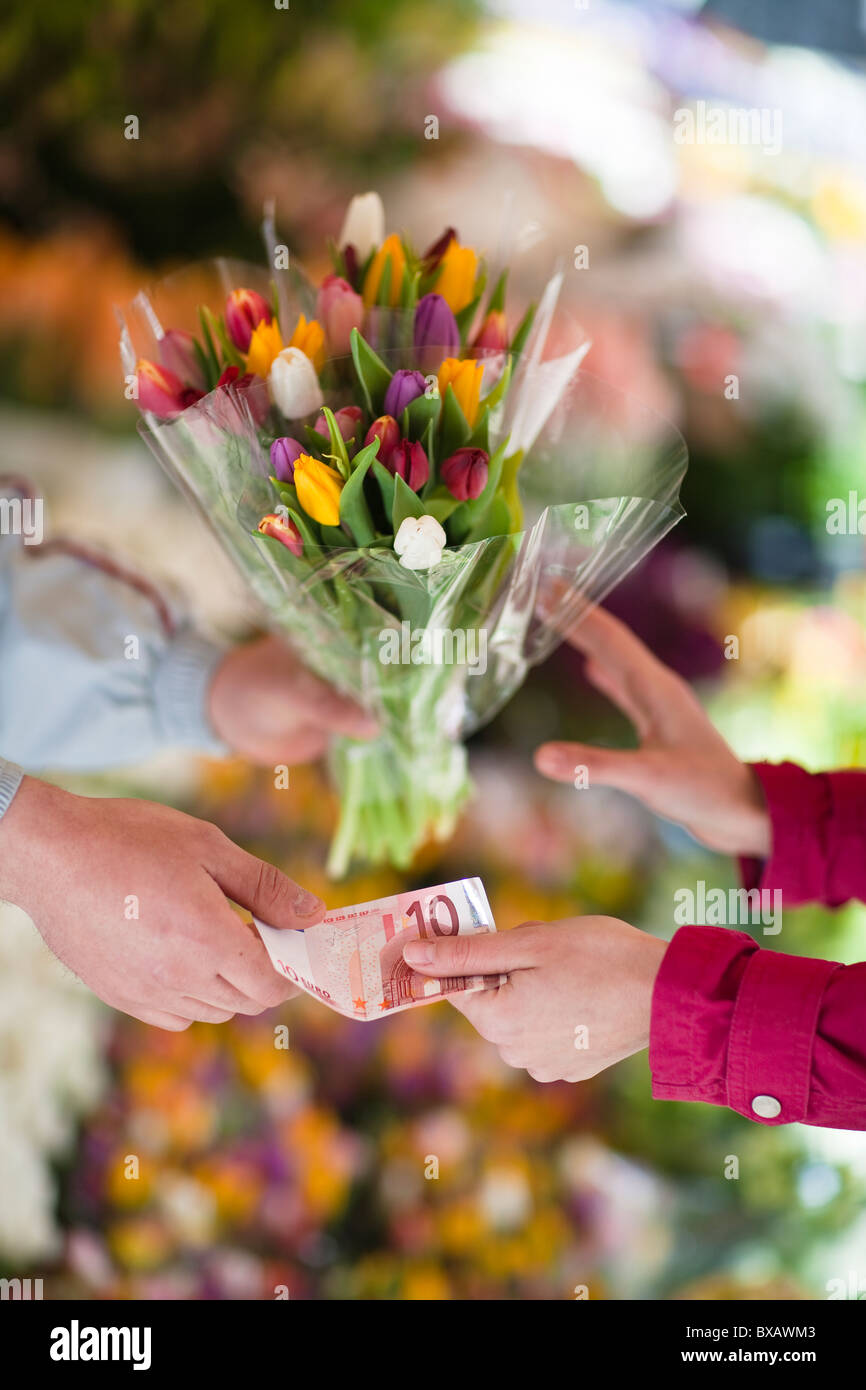 Person buying bunch of flowers from vendor - Stock Image