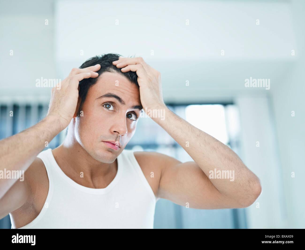 man checking receding hairline - Stock Image
