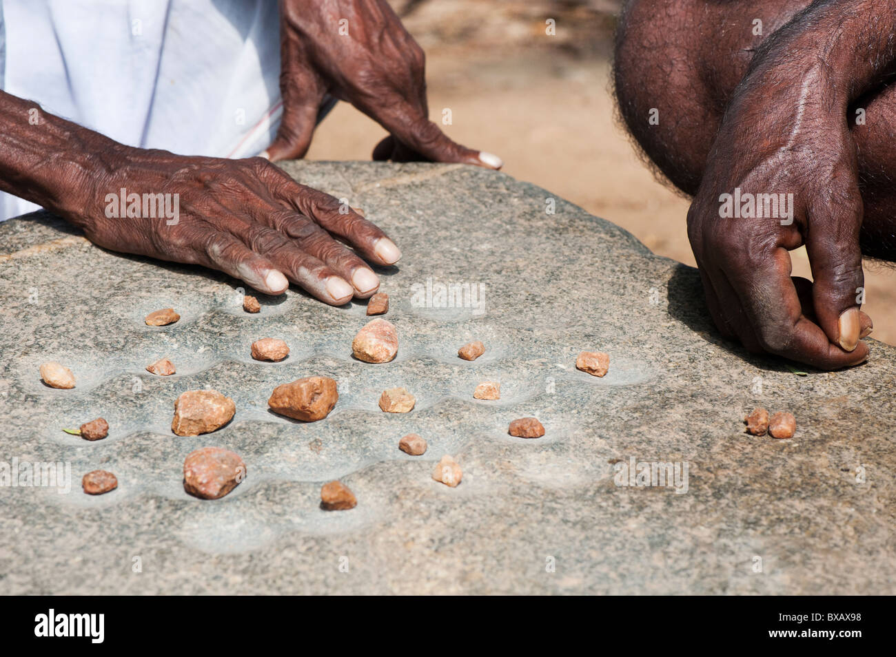 Old game like draughts played with stones by indian men in a rural indian village. Andhra Pradesh, India - Stock Image