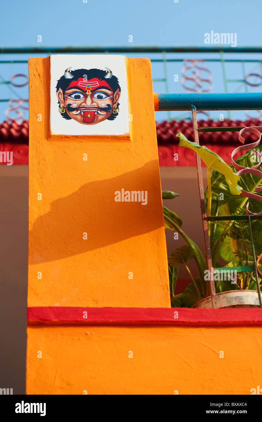 Hindu protection deity ceramic wall tile on the outside of a colourful house. Andhra Pradesh, India - Stock Image