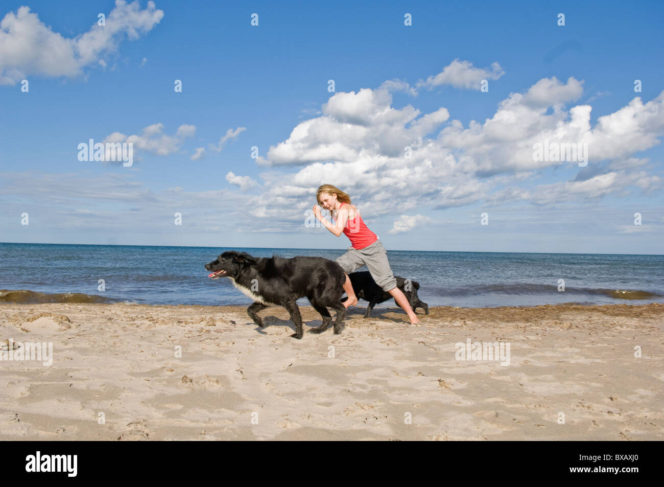 Girl with dogs running on beach Stock Photo
