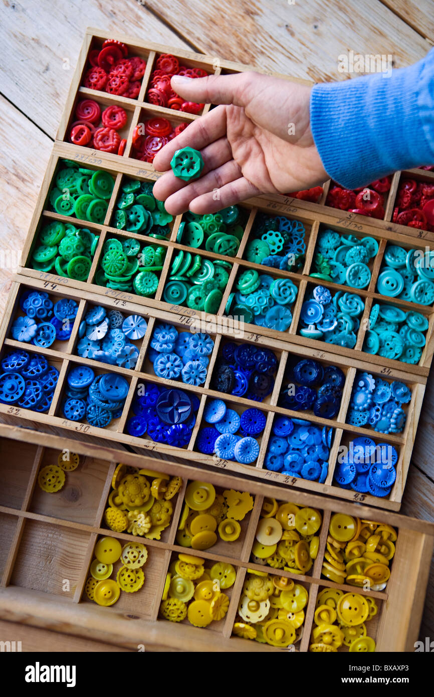 Persons hand browsing box of buttons - Stock Image