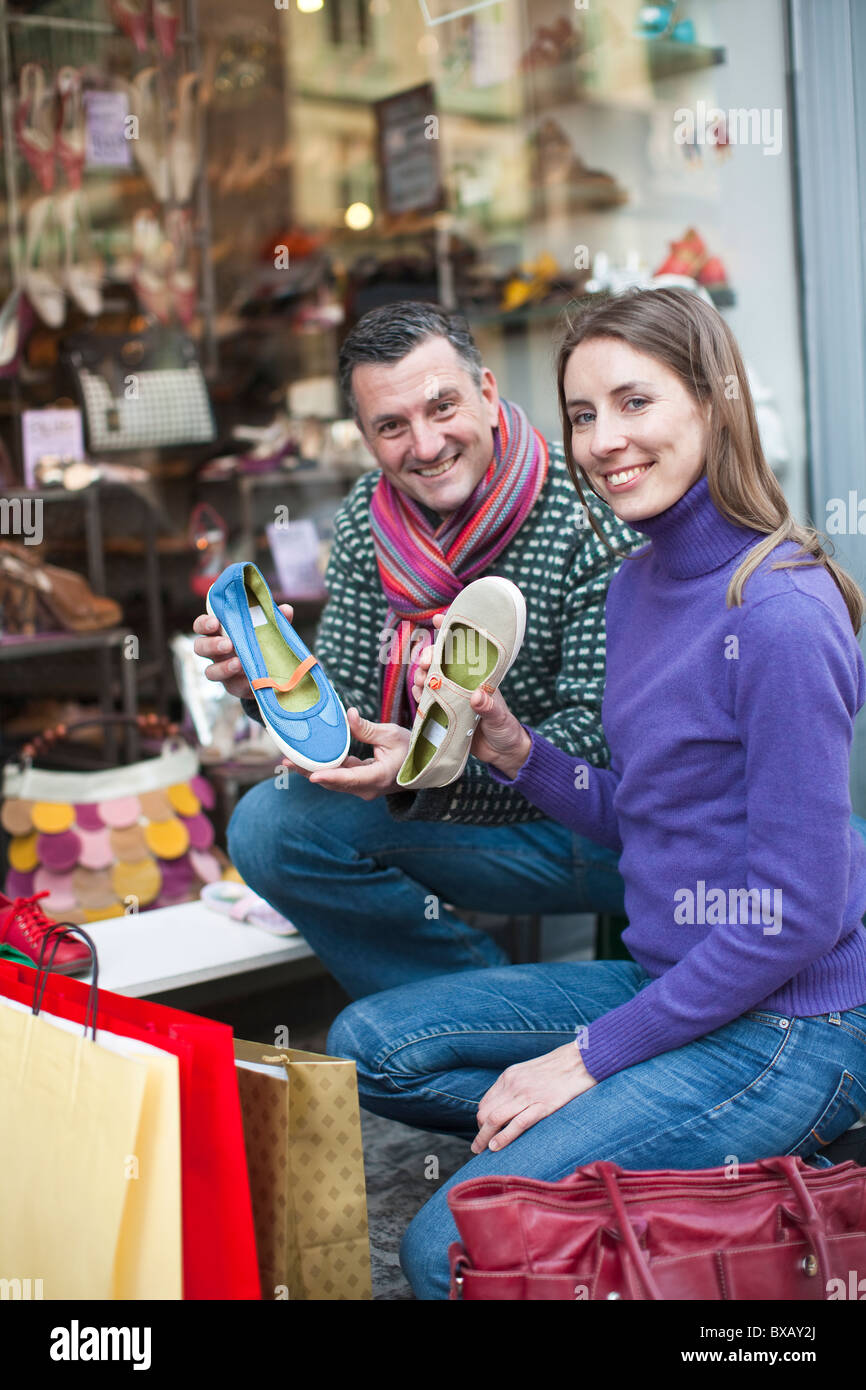 Portrait of couple holding shoes outside shop - Stock Image