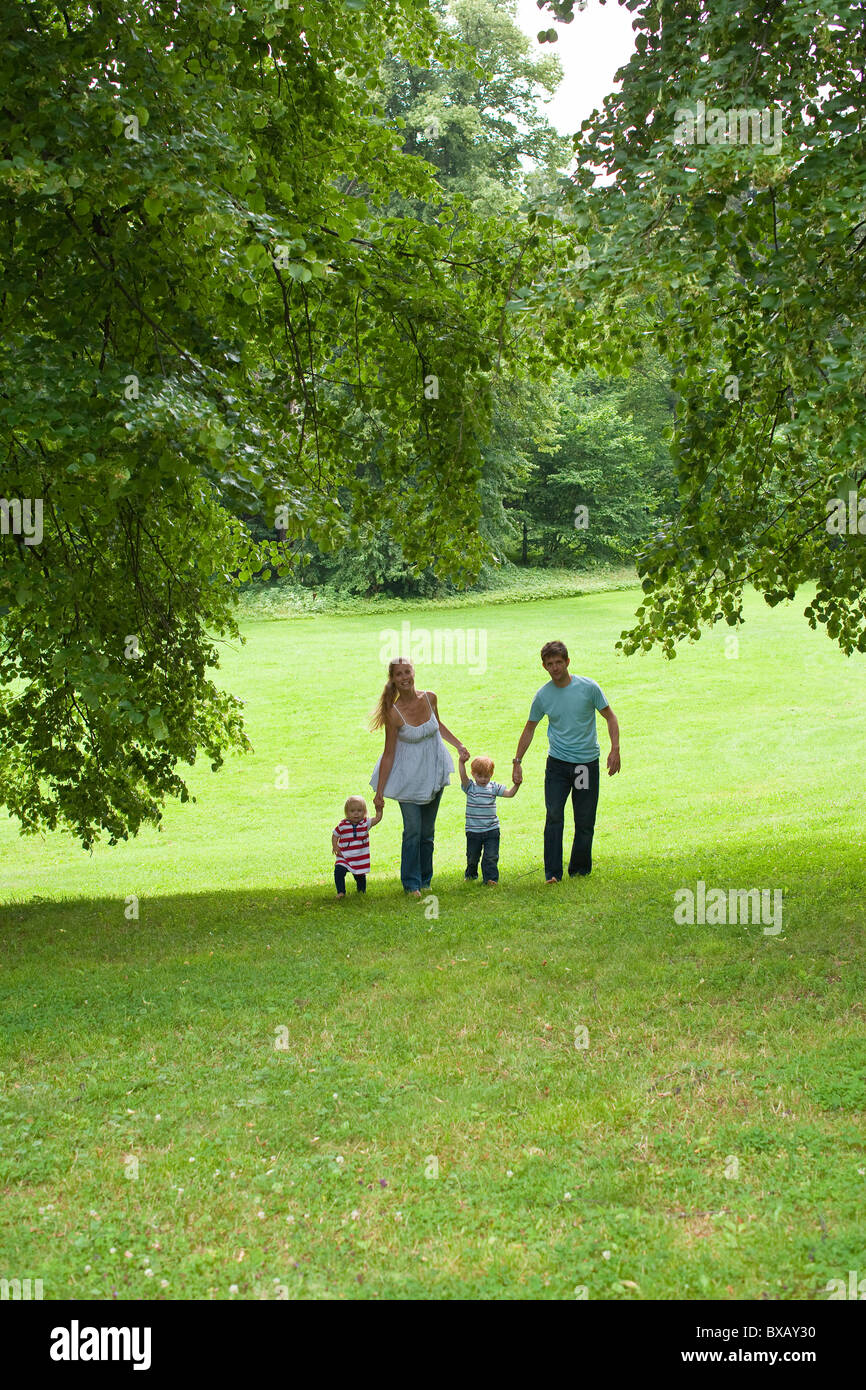 Parents walking with children in park - Stock Image