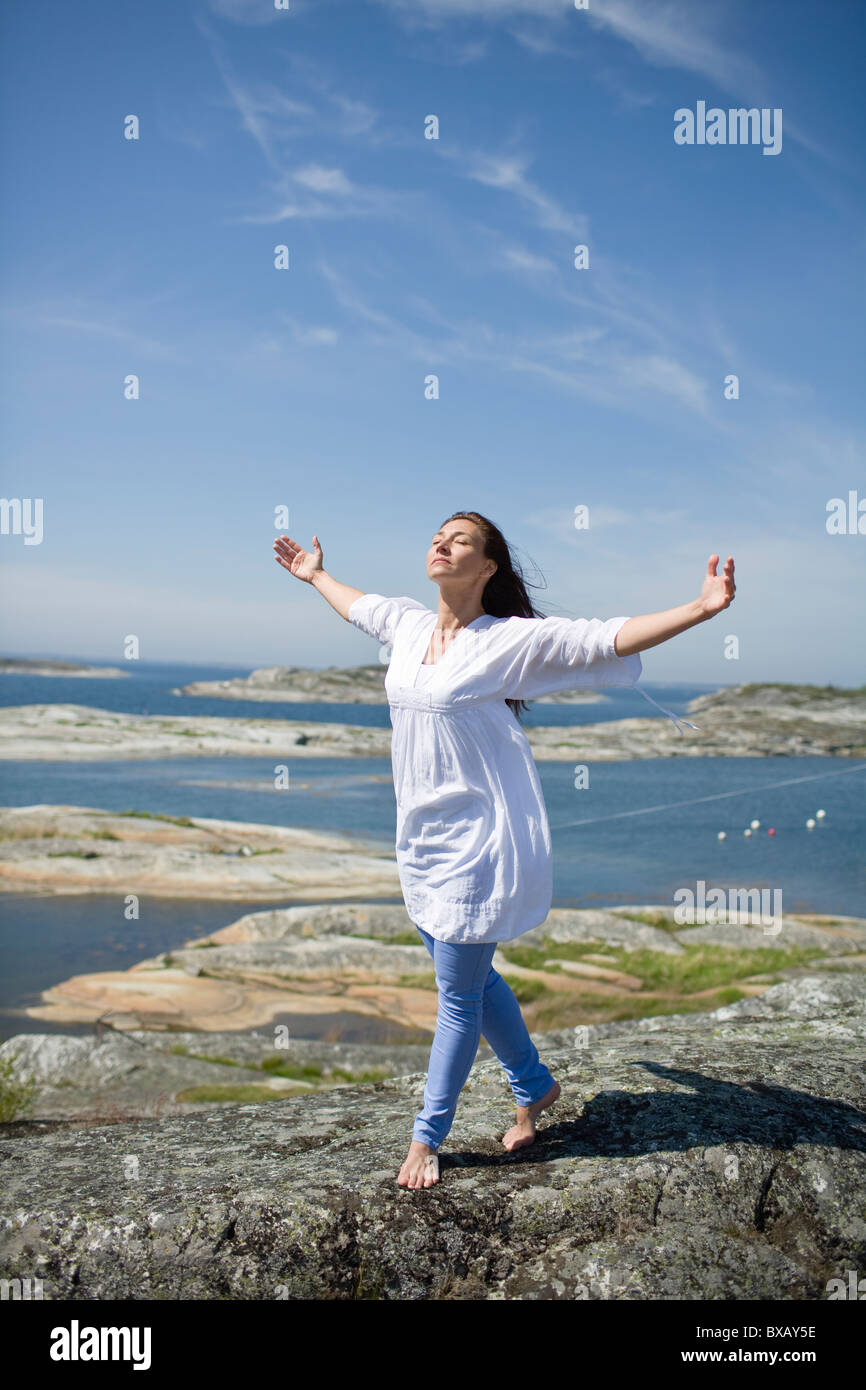 Woman walking on rock with arms up - Stock Image