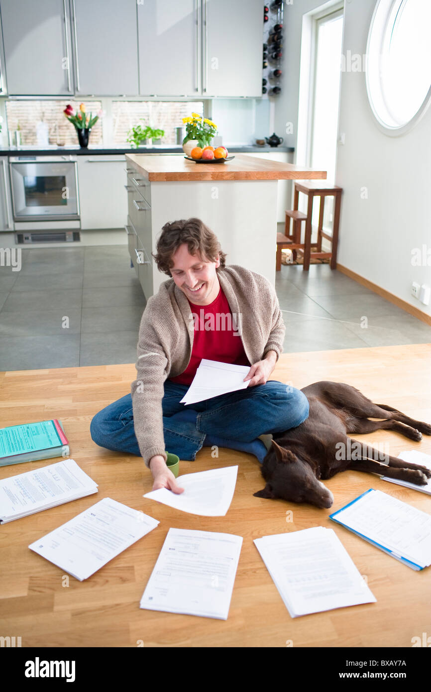 Mid-adult man arranging domestic paperwork on floor, while dog is sleeping next to him - Stock Image