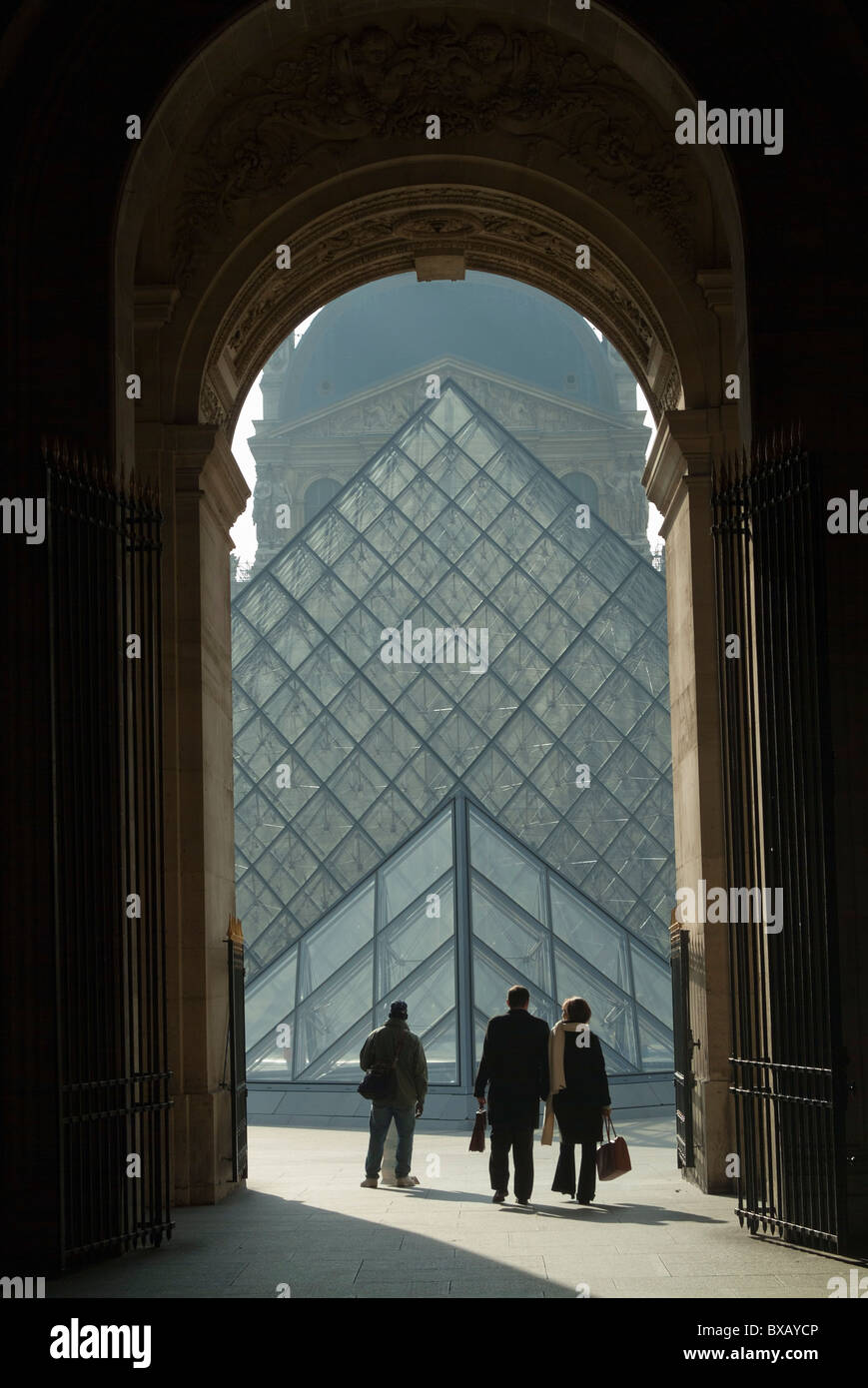 The Louvre Pyramid, seen from a grand archway, Paris, France. - Stock Image