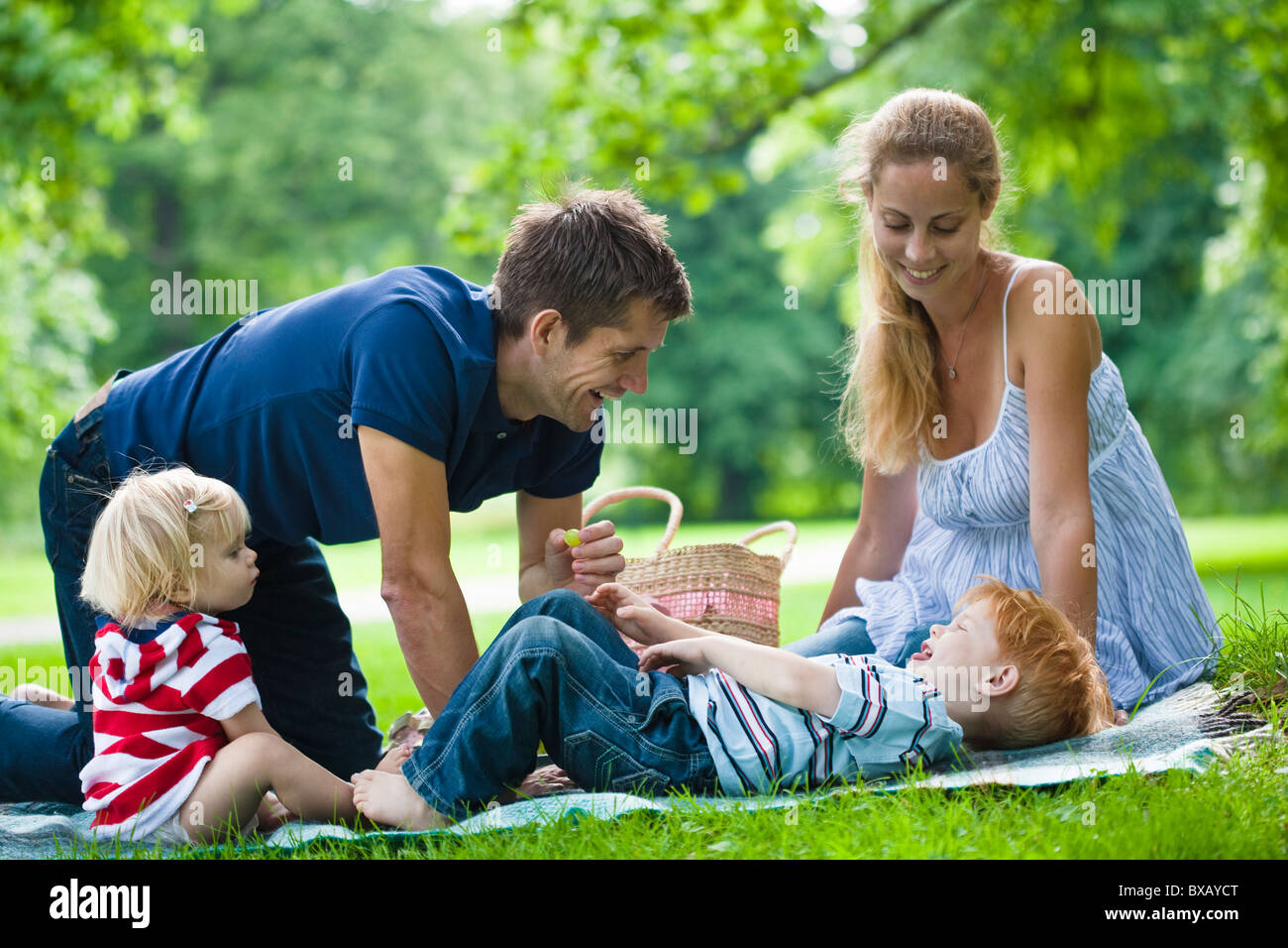 Mid adult parents plying with children during picnic - Stock Image