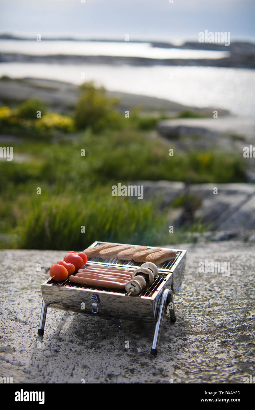 Barbecue grill with meal on rock - Stock Image