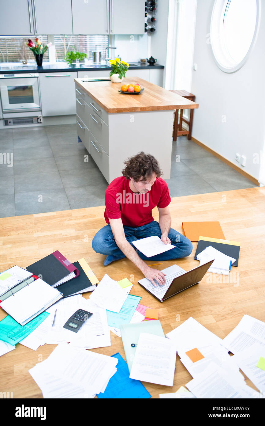 Elevated view of mid- adult man struggling with domestic paperwork - Stock Image