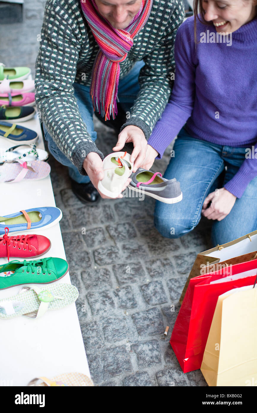 Couple observing shoes at outdoor market stall - Stock Image