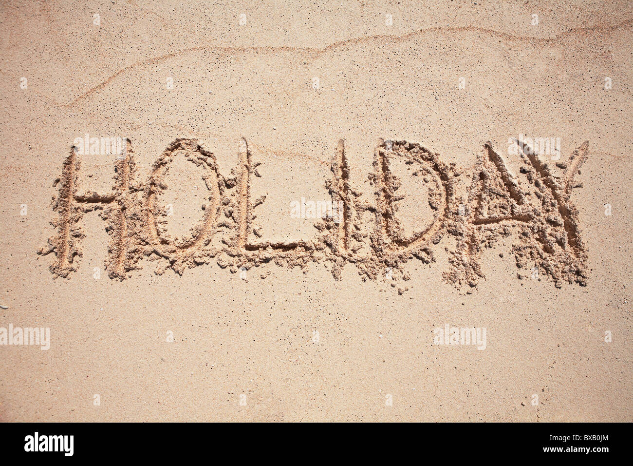 Text  HOLIDAY written on sand - Stock Image