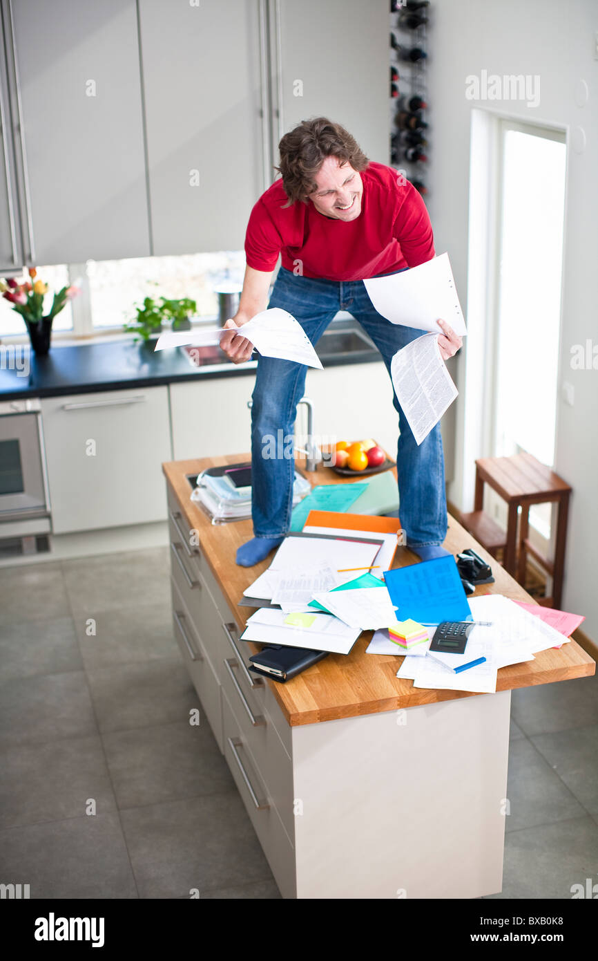 Man struggling with domestic paperwork - Stock Image