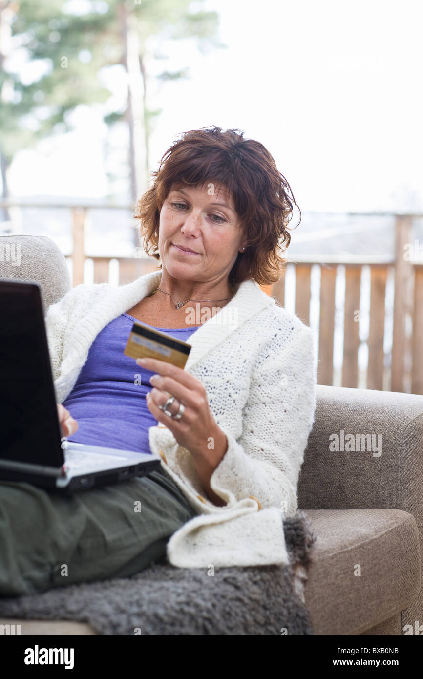 Woman sitting with laptop holding credit card - Stock Image
