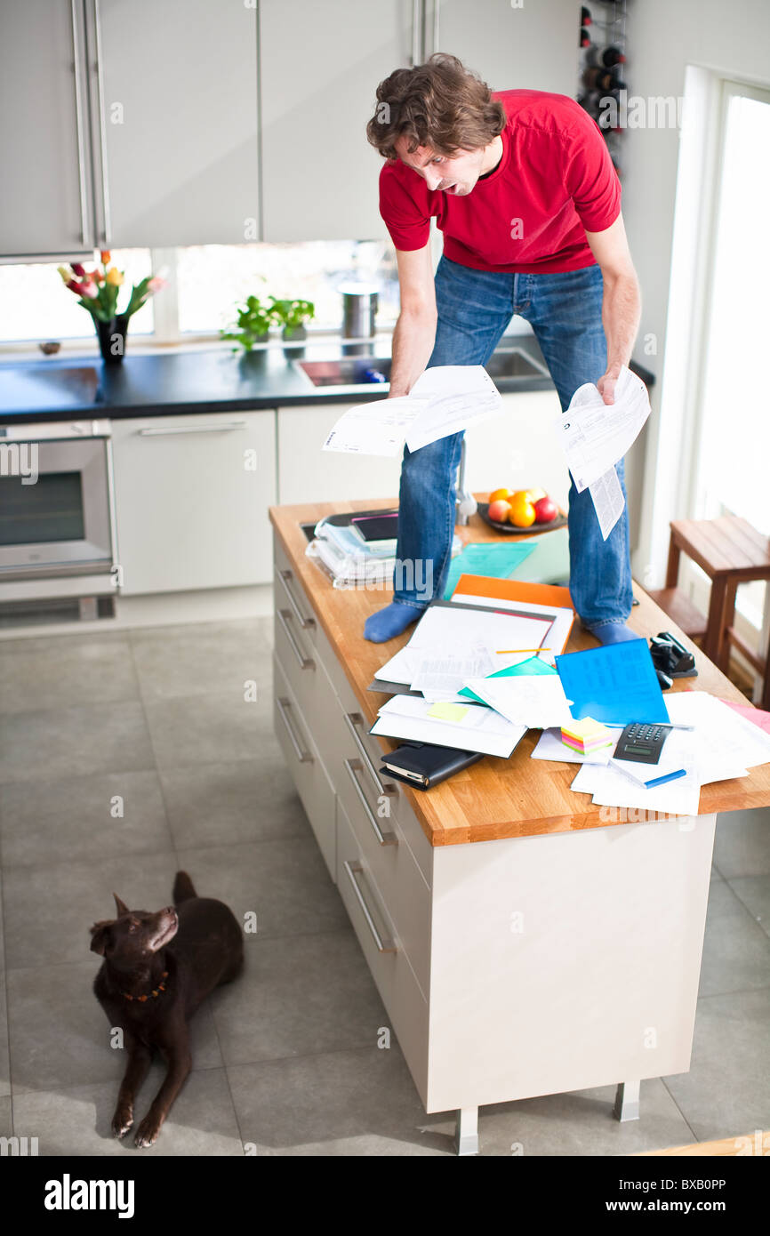 Man struggling with domestic paperwork, while dog is watching - Stock Image