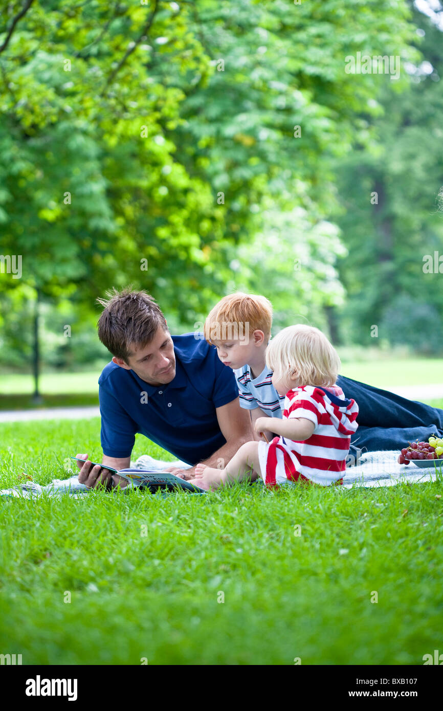 Mid adult father reading  book to children - Stock Image