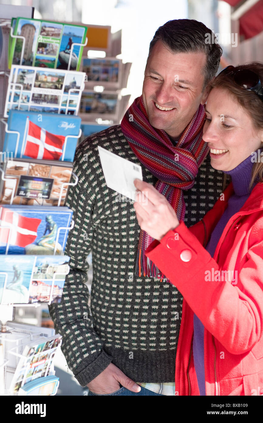 Couple buying postcards from outdoor stall - Stock Image