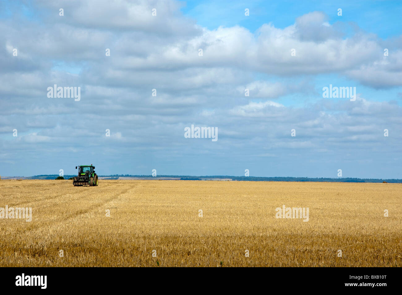 Tractor parked in harvested corn field, Normandy, France. - Stock Image