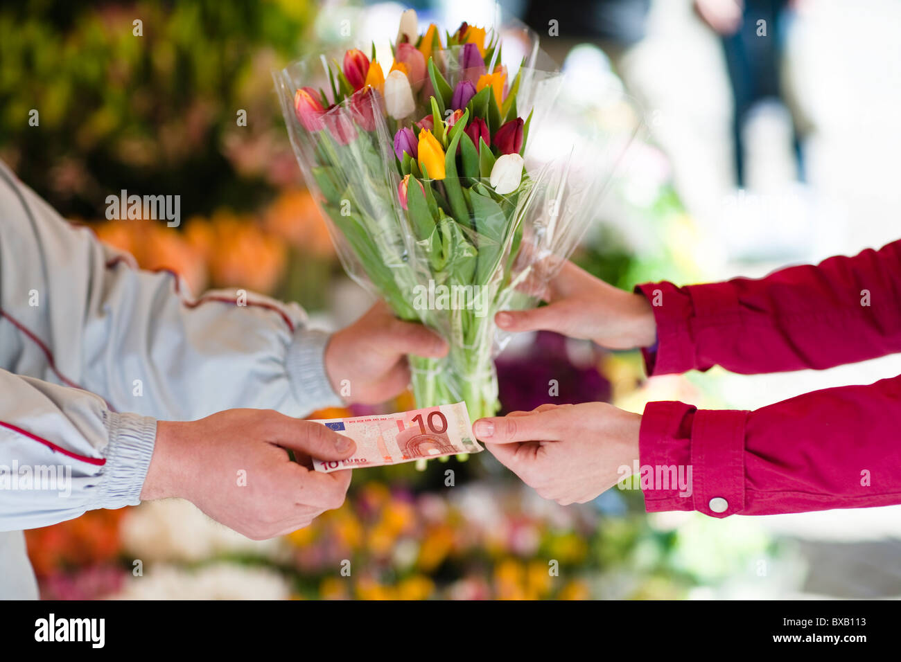 Person buying bunch of flowers from vendor Stock Photo