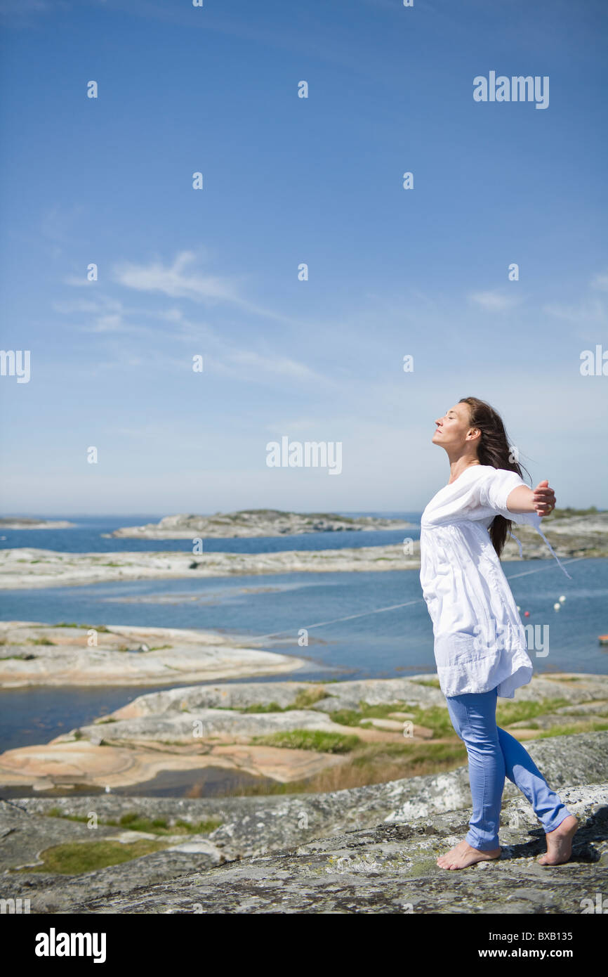 Woman standing on rock with arms up - Stock Image