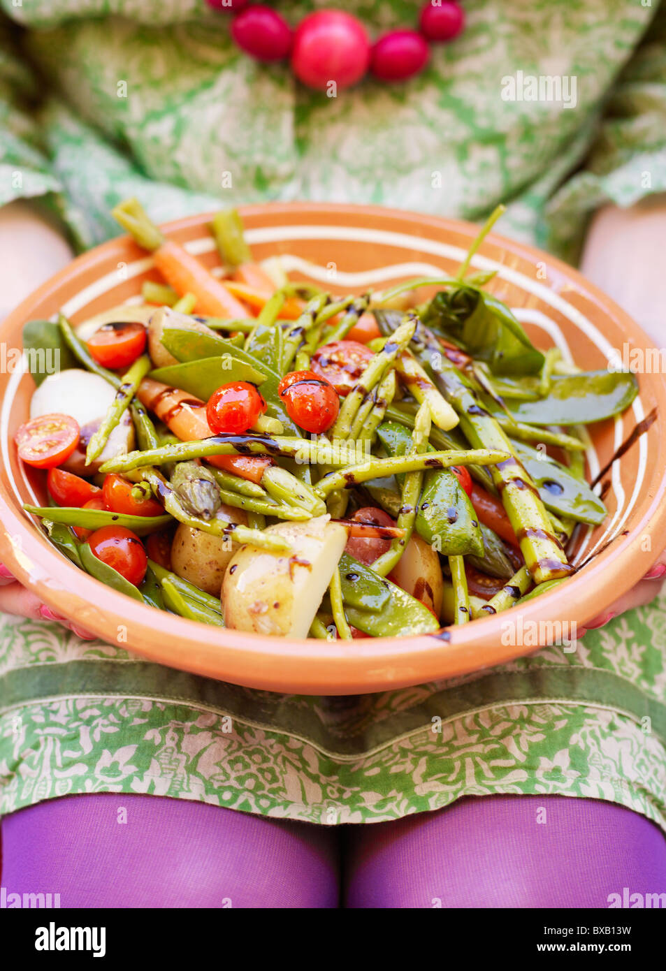 Woman holding plate of vegetable salad - Stock Image