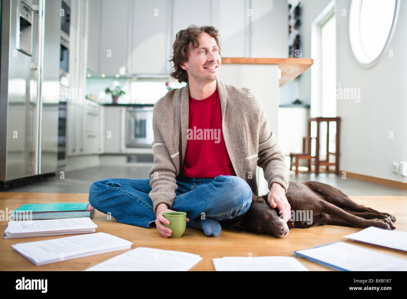 Mid-adult man doing paperwork on floor, while dog is sleeping next to him - Stock Image