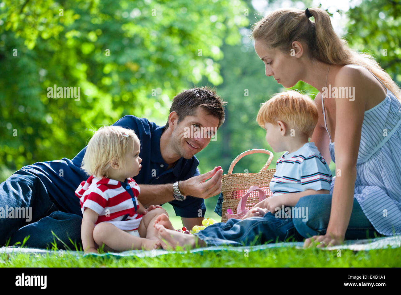 Mid adult parents with children on picnic - Stock Image