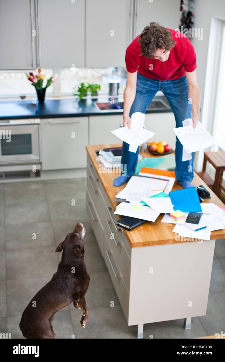 Man struggling with domestic paperwork while dog is watching - Stock Image