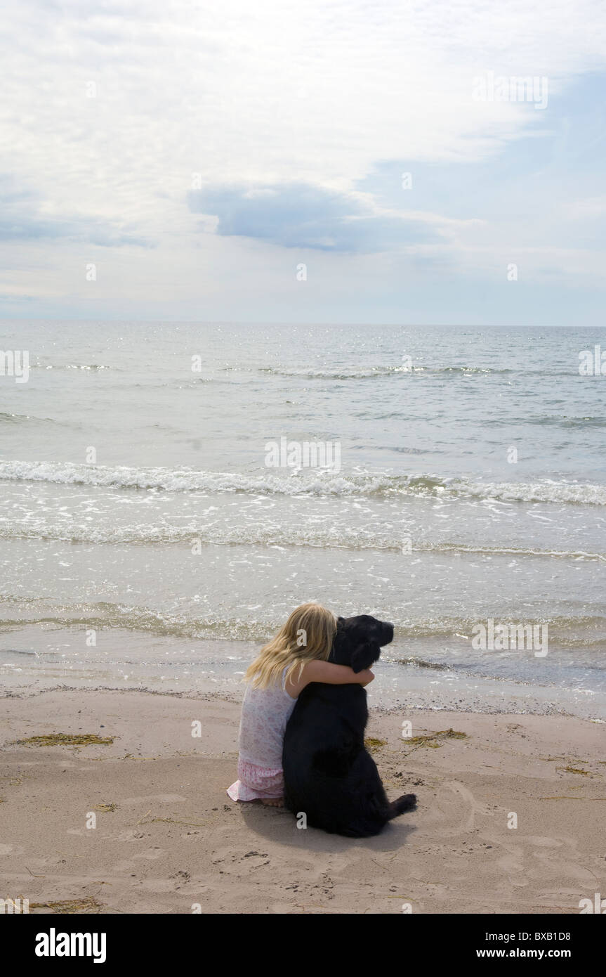 Girl with dog sitting on beach Stock Photo