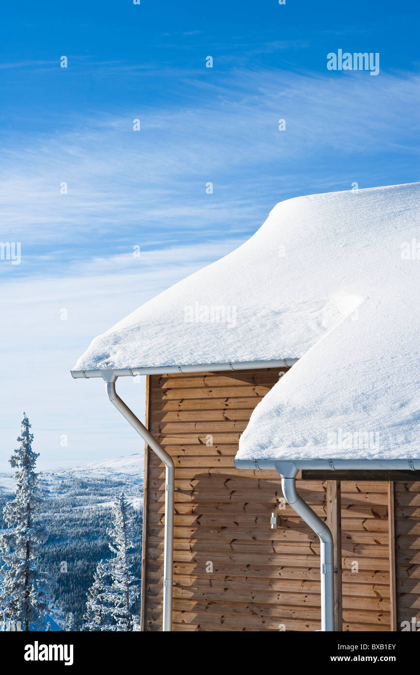 Wooden house covered by snow - Stock Image