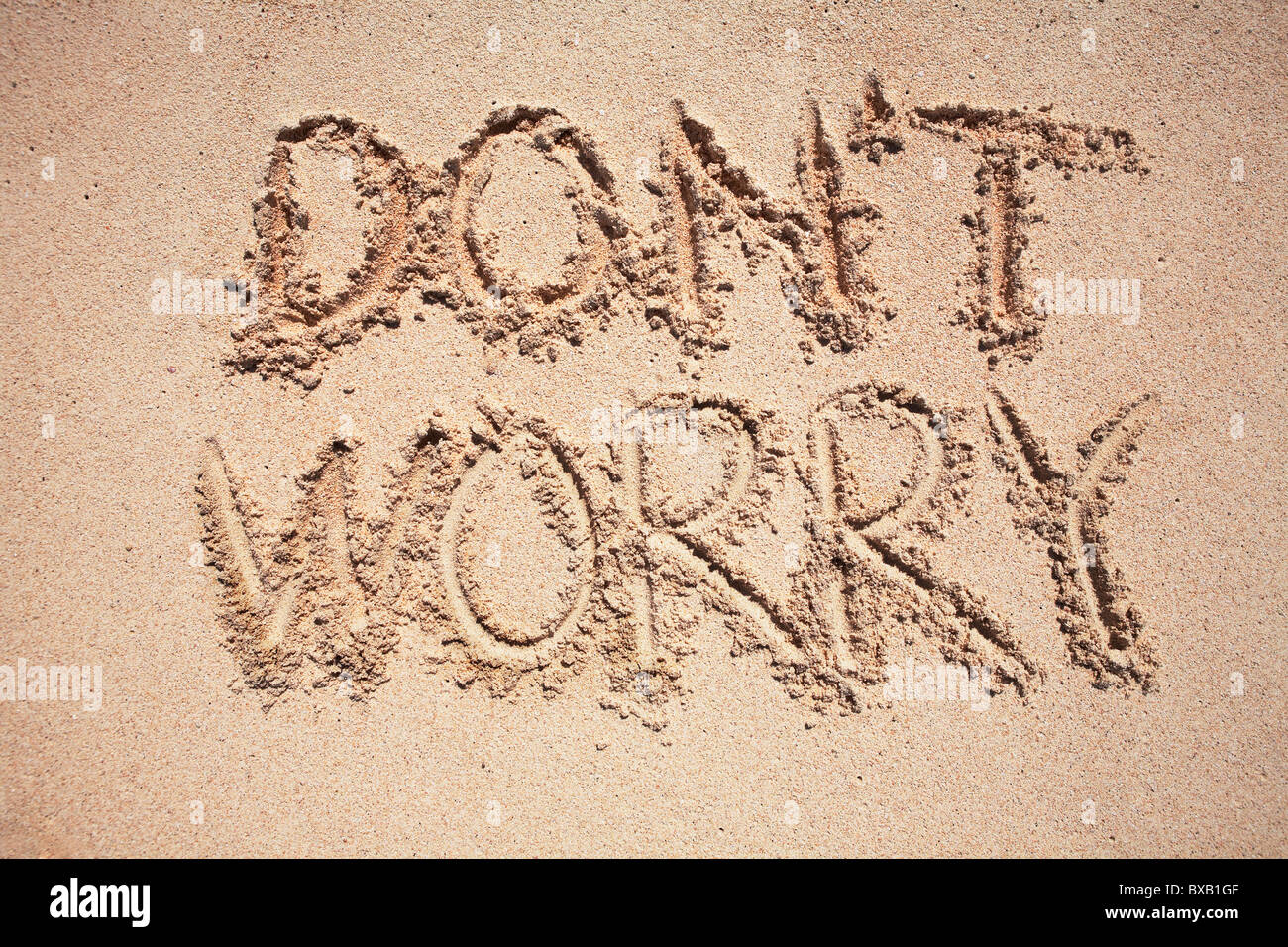 Text dont worry written on sand - Stock Image