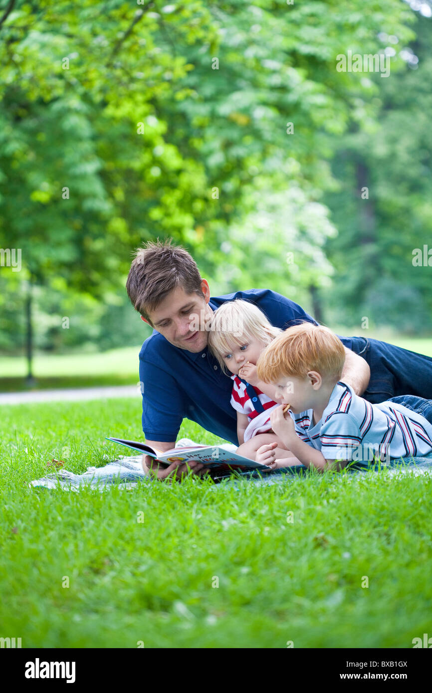 Father reading book to son and daughter in park - Stock Image