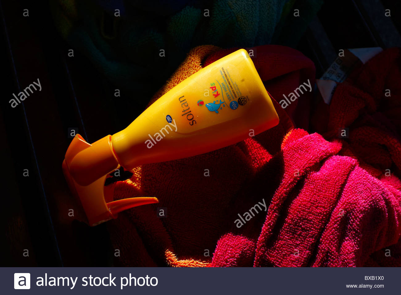 A Bottle of Sun Cream Lotion in the direct sun poolside with a towel - Stock Image