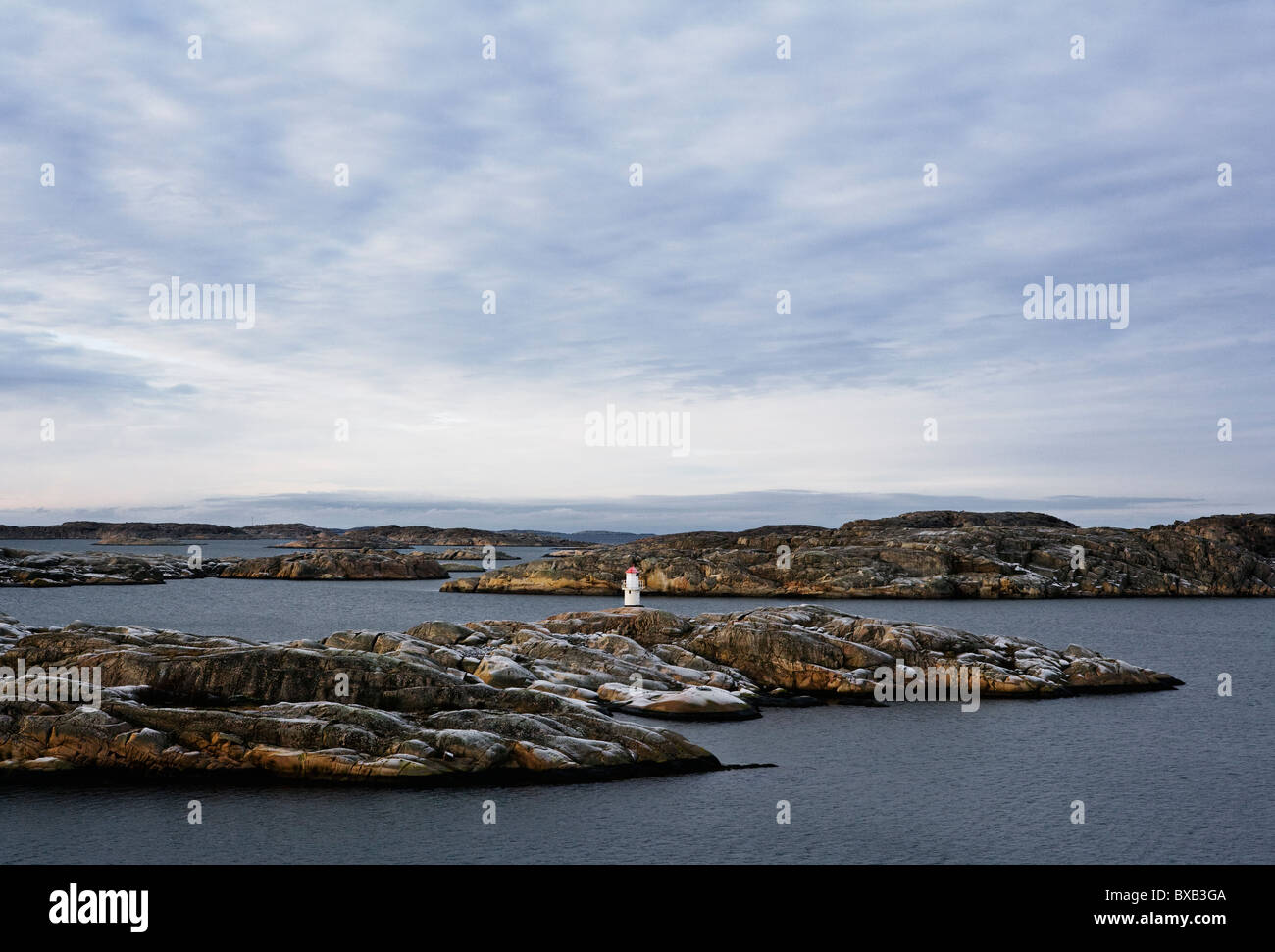 Remote lighthouse on rocks - Stock Image