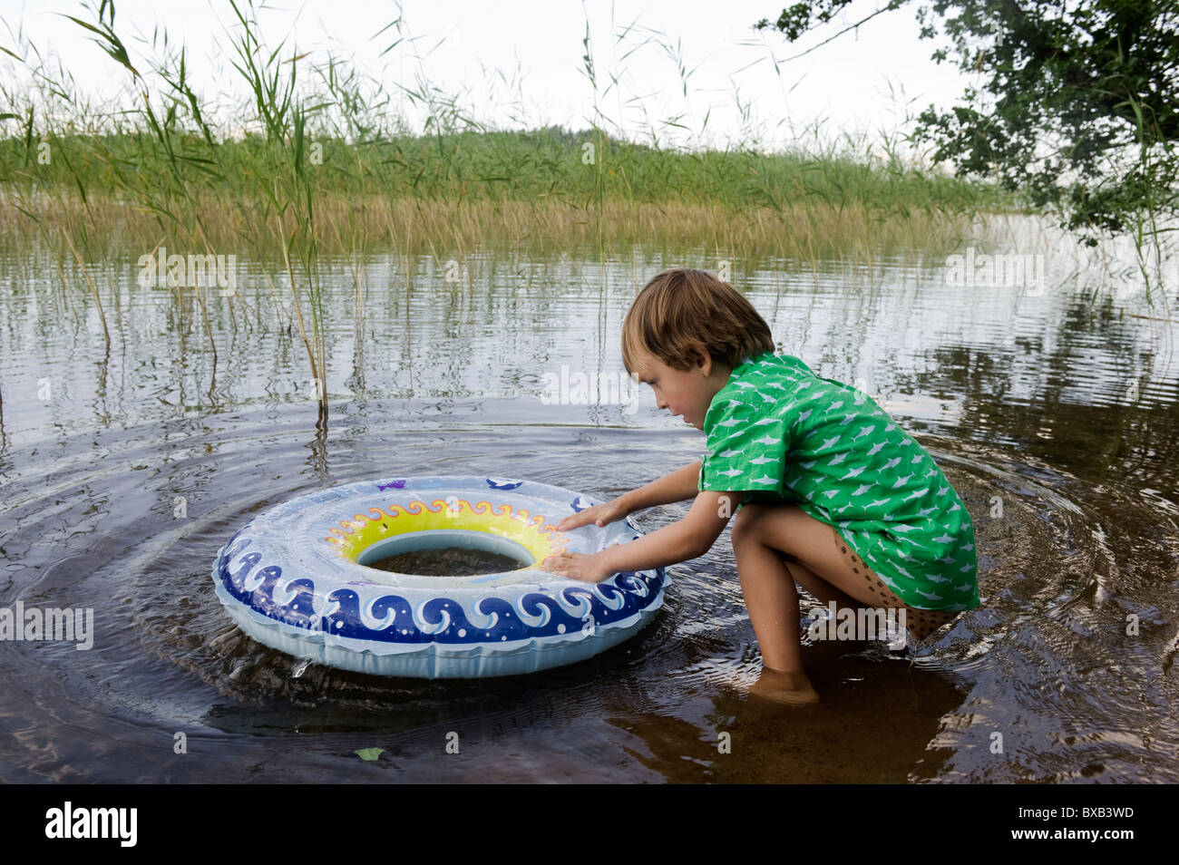 Boy playing with inner tube at edge of lake - Stock Image
