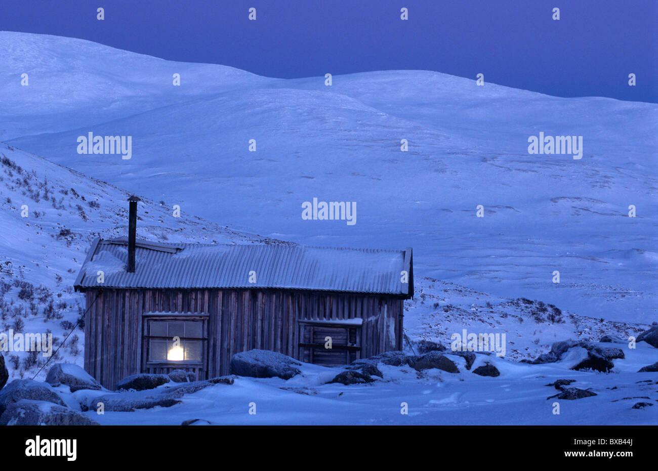 Remote log cabin at dusk - Stock Image