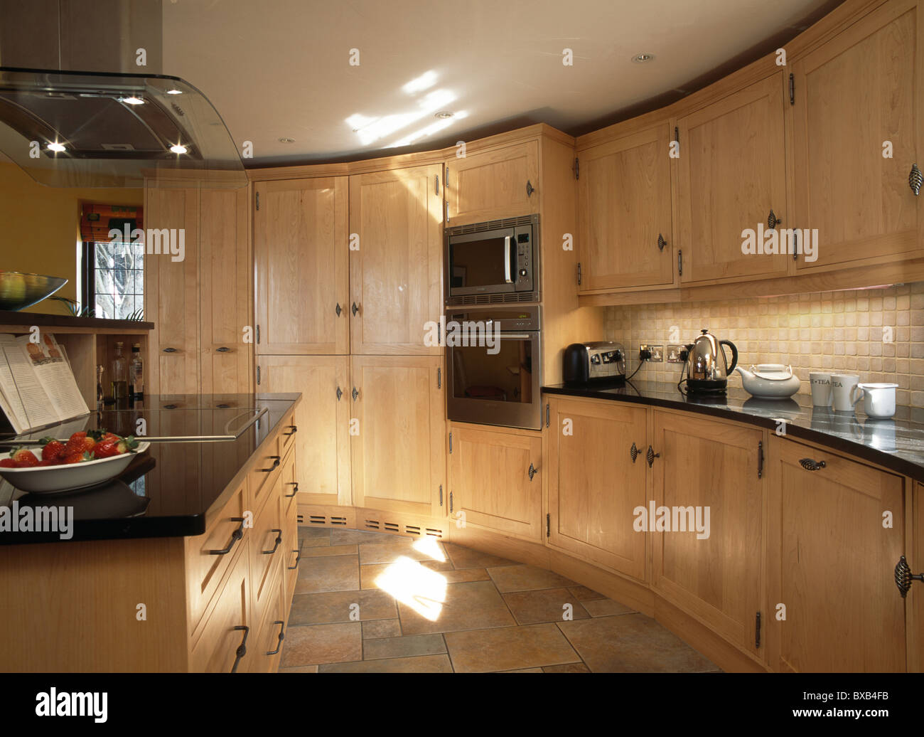 Cream Townhouse Kitchen With Pale Wood Fitted Units On Curved Wall Stock Photo Alamy