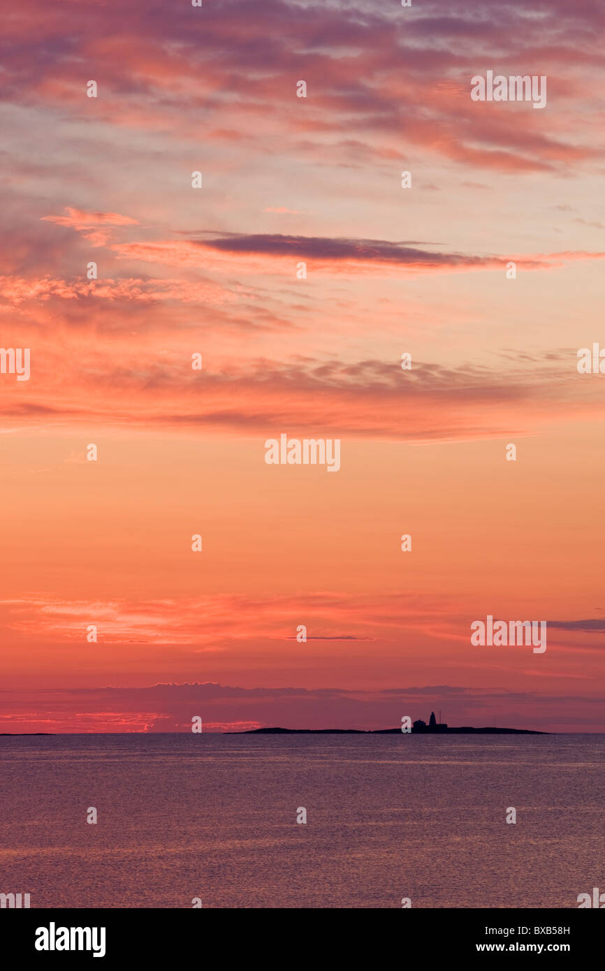 Sunset sky with sea and distant lighthouse - Stock Image