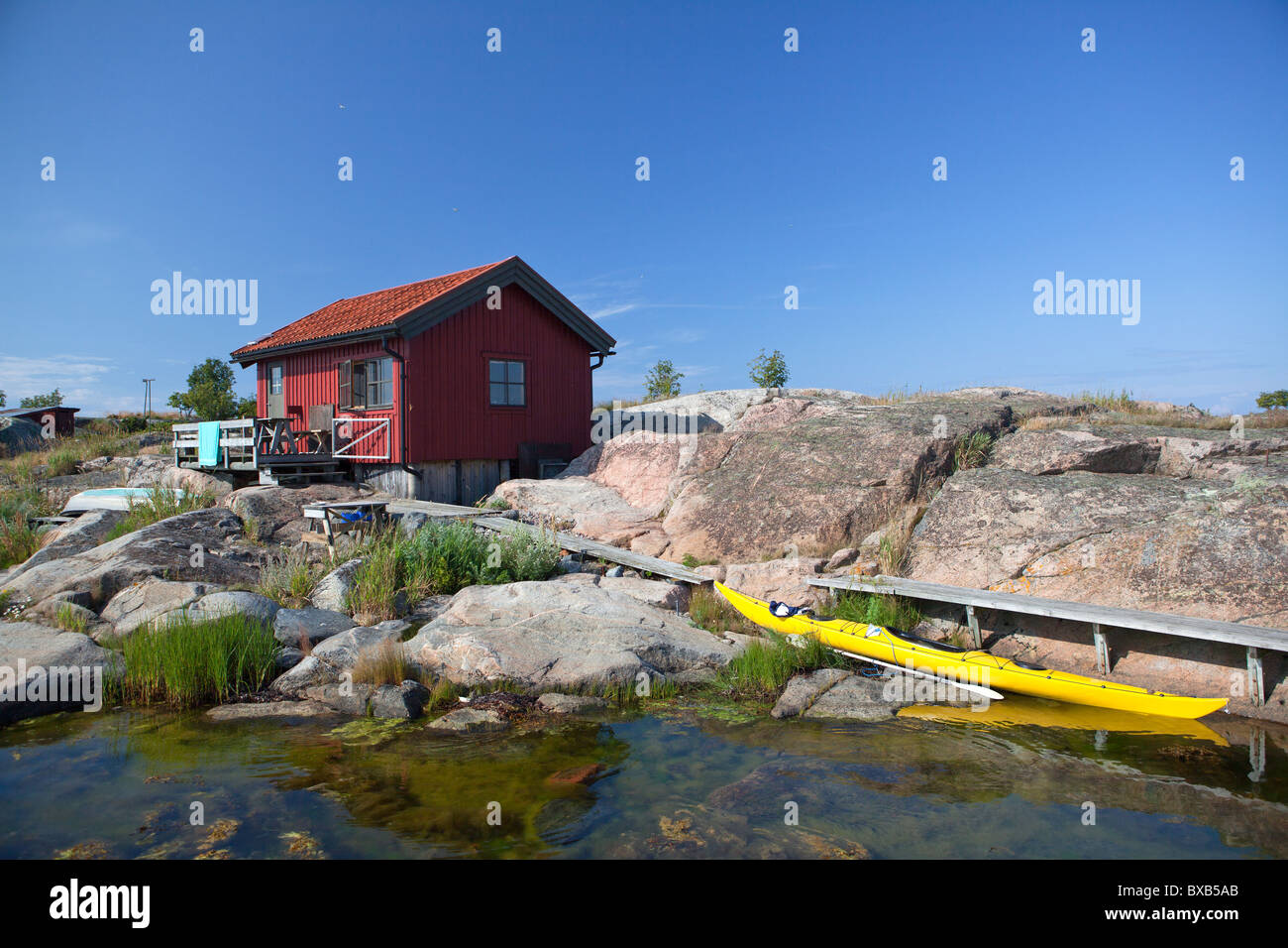 Yellow canoe moored next to small cottage house - Stock Image