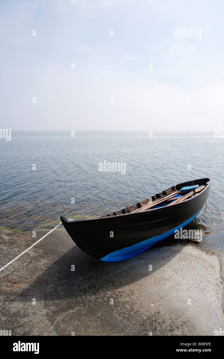 Small boat moored on coast - Stock Image