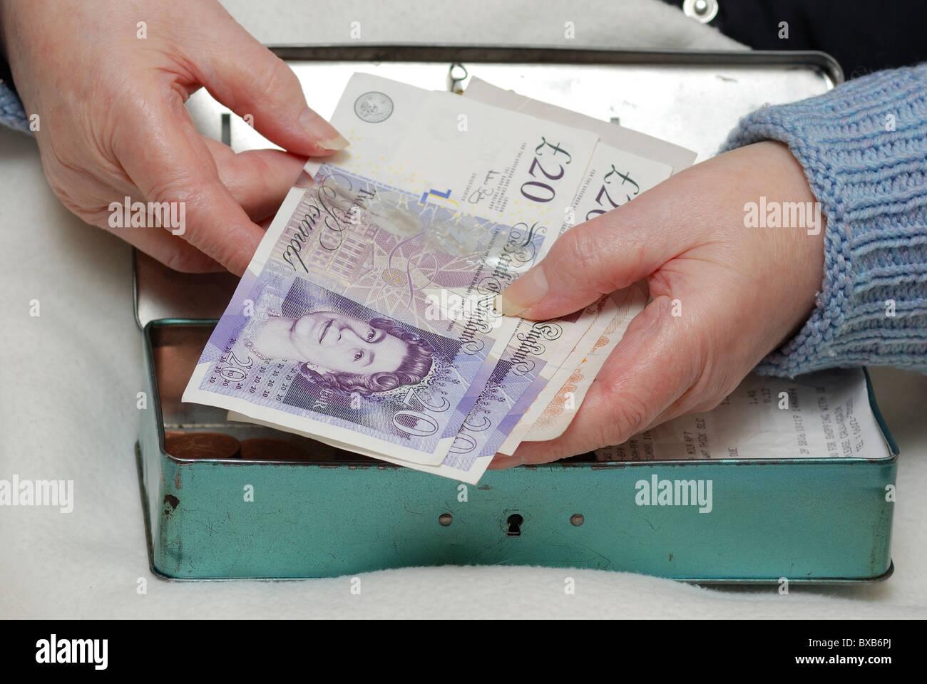 pensioner holding 20 pound notes with cash tin england uk - Stock Image