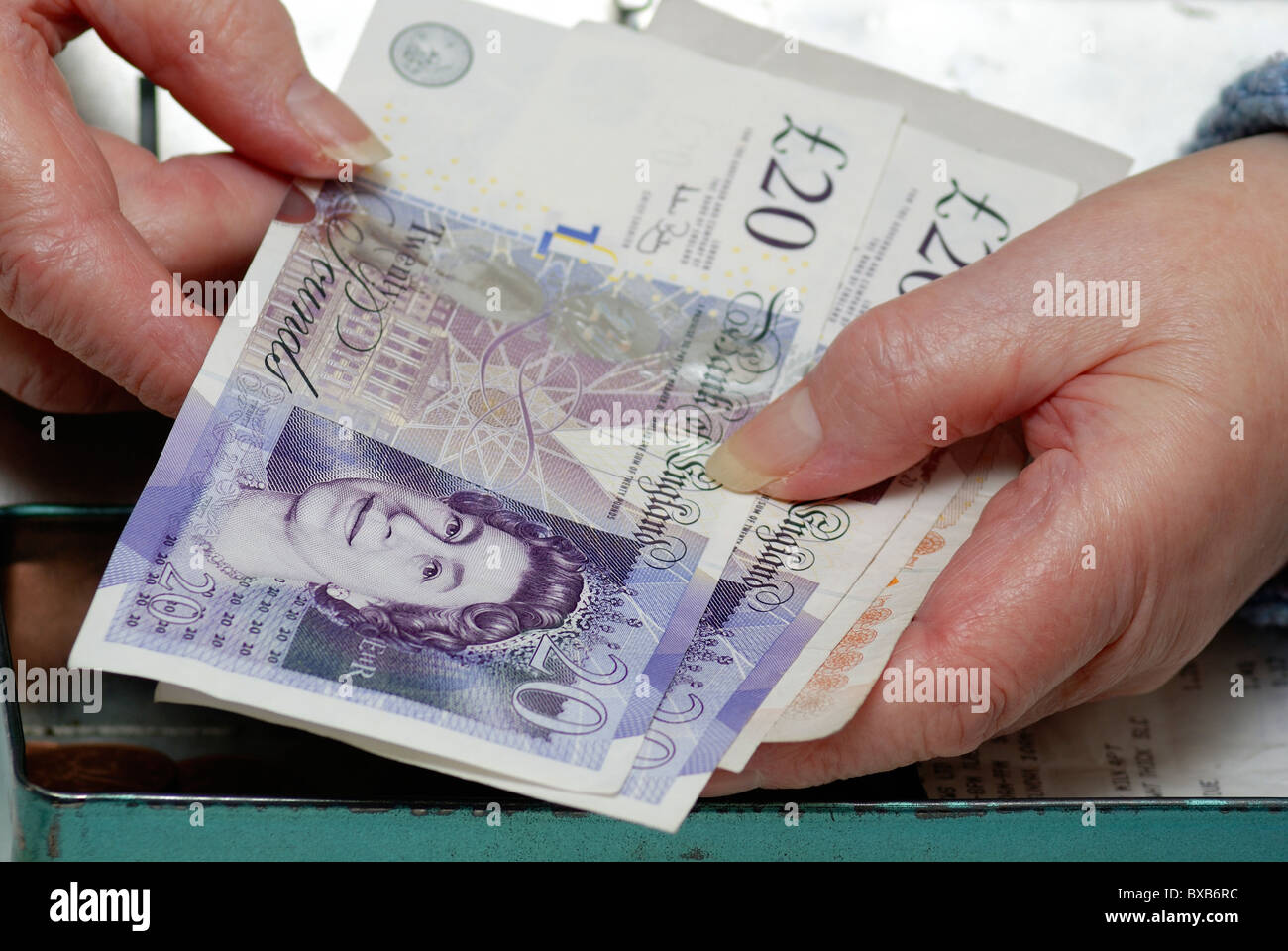 pensioner holding 20 pound notes English currency uk - Stock Image