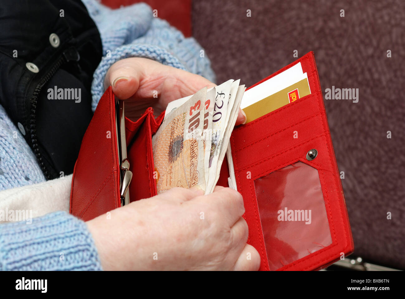 pensioner with open purse showing English currency notes - Stock Image