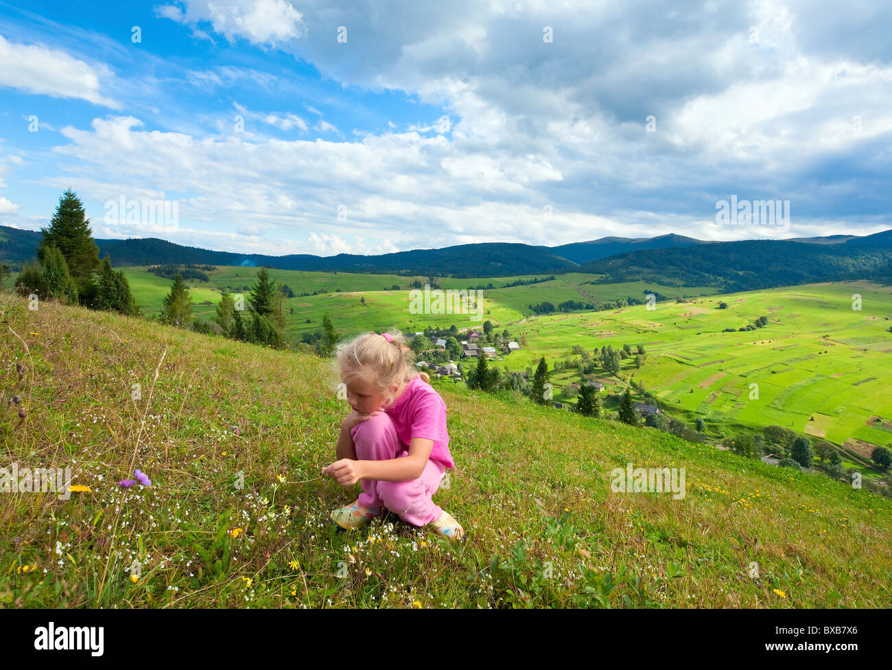 Schoolage girl in a summer mountain walk - Stock Image
