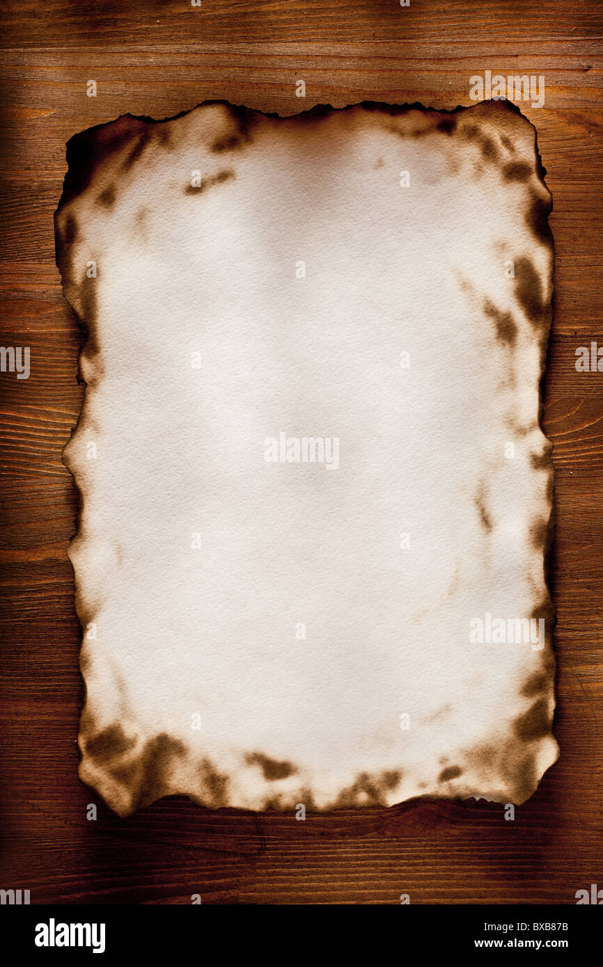 Burnt at the edges textured paper against a wooden wall - Stock Image